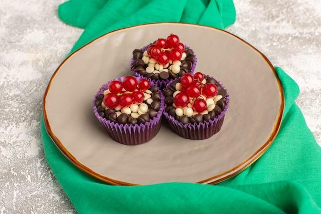 Вид сверху шоколадные пирожные с клюквой внутри тарелки светлый стол с зеленой салфеткой, печенье, бисквит, сладкое тесто для выпечки Бесплатные Фотографии