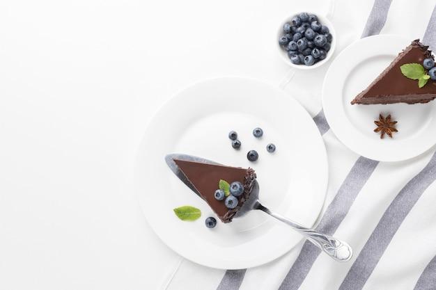 Vista dall'alto di fette di torta al cioccolato su piastre con mirtilli Foto Gratuite