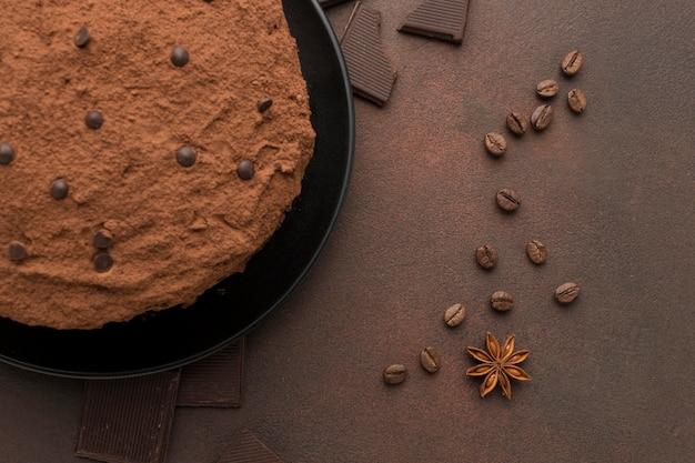 Vista dall'alto della torta al cioccolato con cacao in polvere e chicchi di caffè Foto Gratuite