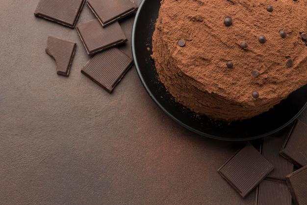 Vista dall'alto della torta al cioccolato con cacao in polvere e copia spazio Foto Gratuite
