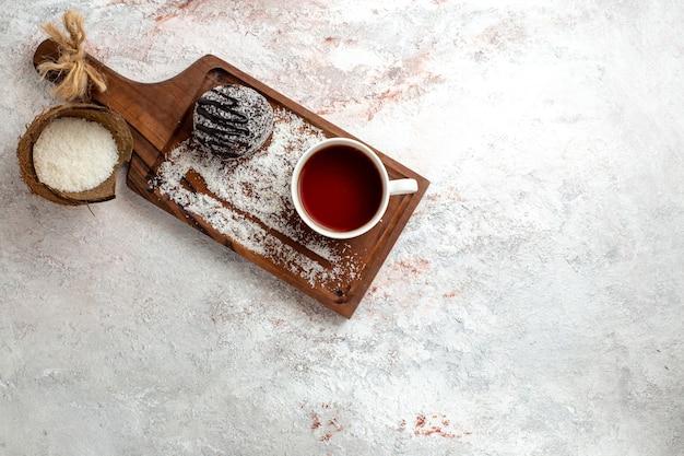 Torta al cioccolato vista dall'alto con una tazza di tè su sfondo bianco torta al cioccolato biscotto zucchero biscotto dolce tè Foto Gratuite