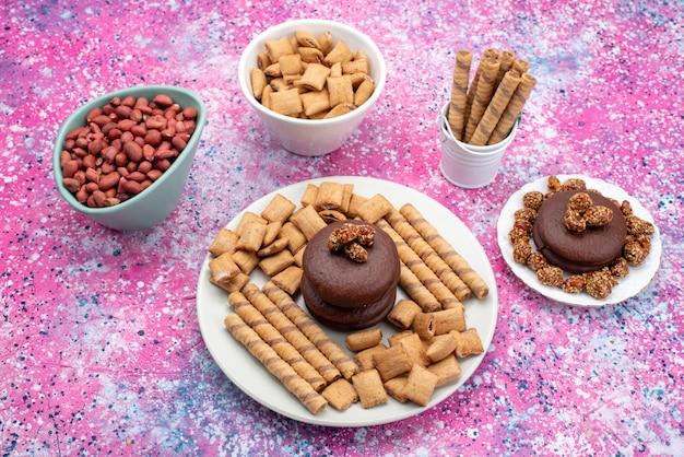 色付きの背景クッキービスケット甘いスナック色のクッキーピーナッツと一緒にトップビューチョコレートケーキ 無料写真