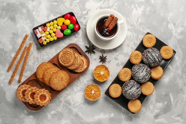 Top view chocolate cakes with cookies candies and cup of tea on white surface Free Photo