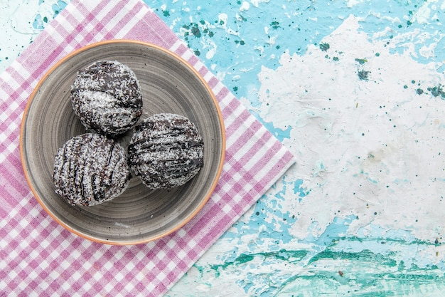 水色の背景のケーキチョコレートビスケット砂糖甘い色の上のアイシングと砂糖粉とトップビューチョコレートケーキ 無料写真