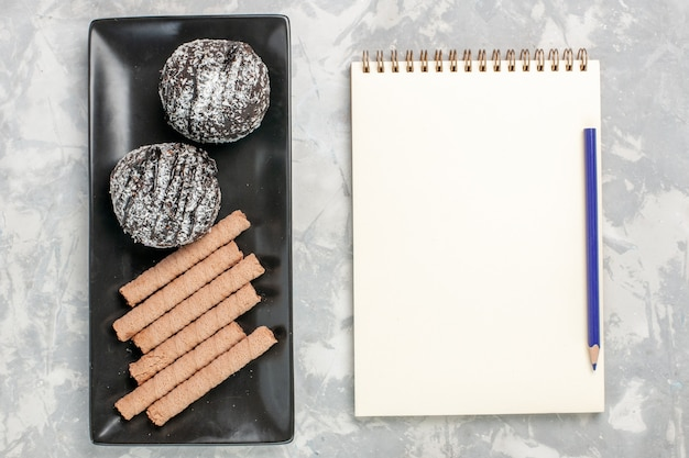 白い表面に甘いパイプクッキーとトップビューチョコレートケーキ 無料写真