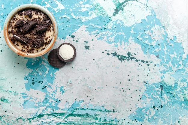 水色の背景のプレートの中にクリームとクッキーが入った上面チョコレートクッキーデザートケーキデザートシュガースウィートカラー写真 無料写真