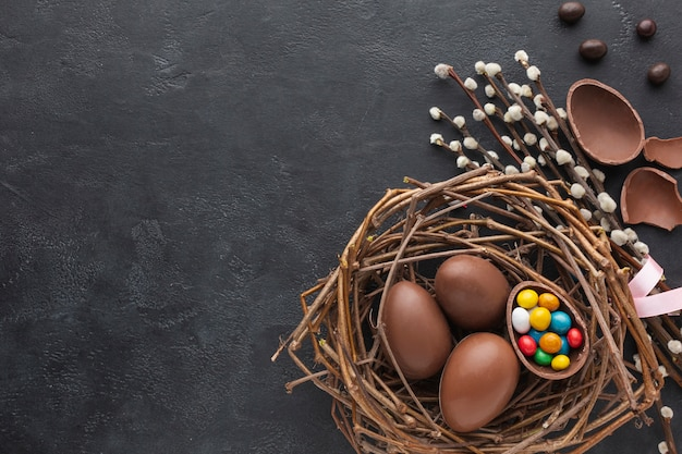 Top view of chocolate easter eggs in nest with candy and flowers Premium Photo