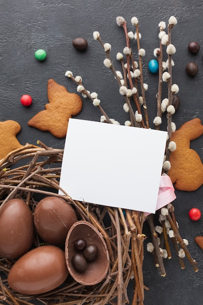 Top view of chocolate easter eggs in nest with cookies and piece of paper on top Premium Photo