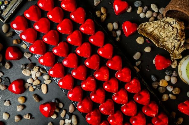 小石とスタンドに赤いハートの形をしたチョコレートのトップビュー 無料写真
