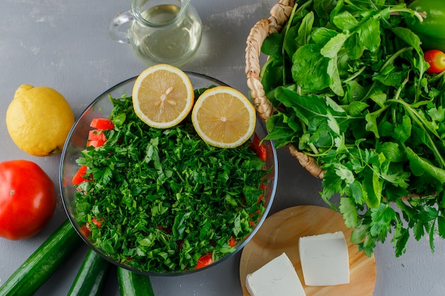 Вид сверху нарезанная зелень в стеклянной посуде с помидорами, сыром, лимоном на серой поверхности Бесплатные Фотографии