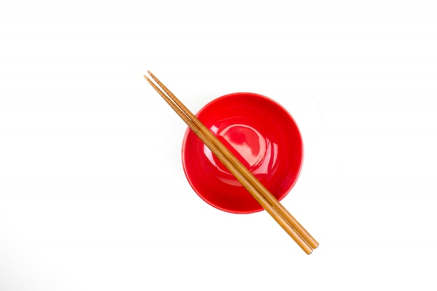 Top view of chopsticks placed on a red bowl. Premium Photo