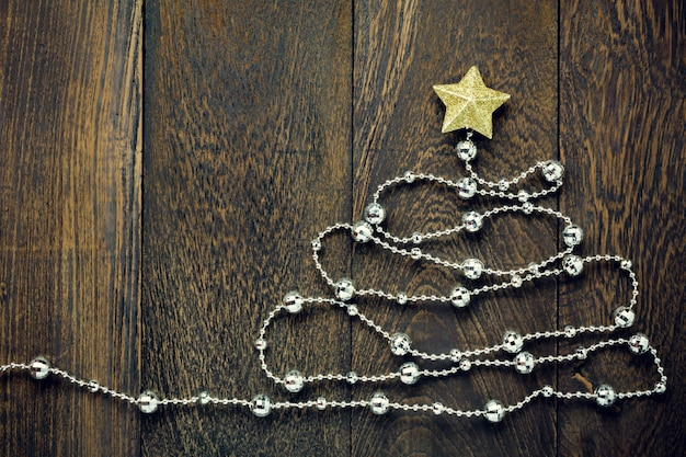 Top view christmas background.fir tree by christmas  decorations,christmas gold star and jewelry clothesline on wooden table background with copy space. Premium Photo