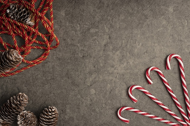 Top view of christmas background with candy canes and pine cones Free Photo