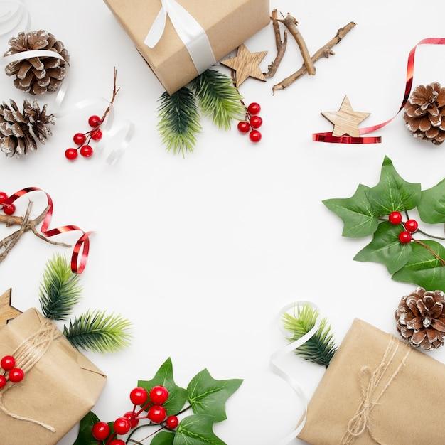 Vista dall'alto della composizione in natale con confezione regalo, nastro, rami di abete, coni, anice sul tavolo bianco Foto Gratuite