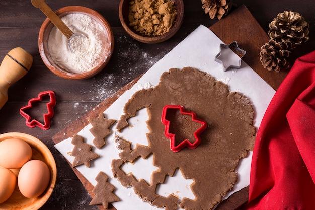 Vista dall'alto della pasta biscotto di natale con forme di albero di natale Foto Gratuite