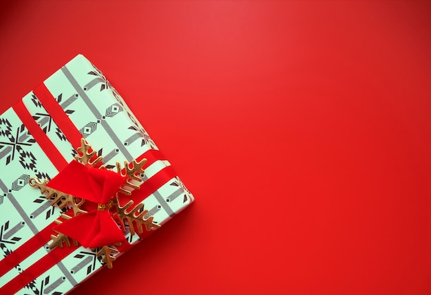 Top view of christmas gift box with red ribbon and bow and golden snow flake Premium Photo