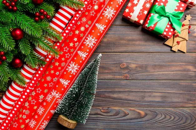 Top view of christmas made of fir tree, rolled wrapping paper and other decorations on wooden. Premium Photo