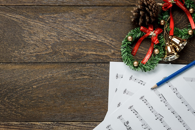 Top view christmas music note paper with christmas wreath on wooden background and copy space ...