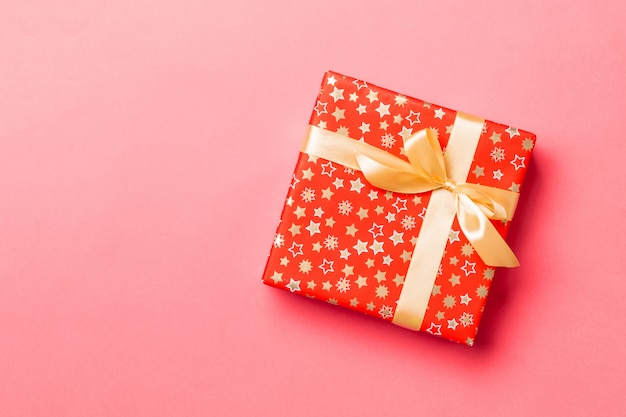 Top view christmas present box with gold bow on living coral background with copy space Premium Photo