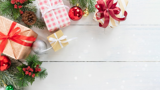 Top view of christmas tree and new year holidays gift box with decorative ornament on wood Premium Photo