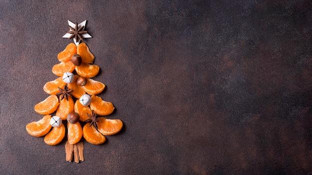 Vista dall'alto della forma dell'albero di natale fatta di mandarini con spazio di copia Foto Gratuite