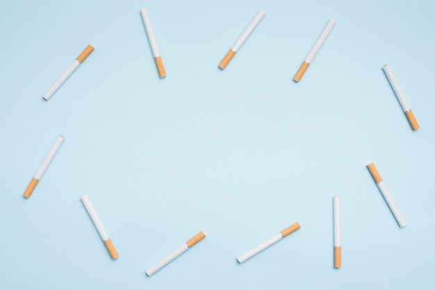 Top view of cigarettes arranged on blue background Free Photo