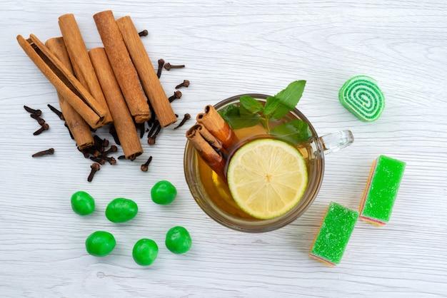 Una vista dall'alto cannella e tè con limone e marmellata sulla scrivania bianca, tè dolce caramelle Foto Gratuite