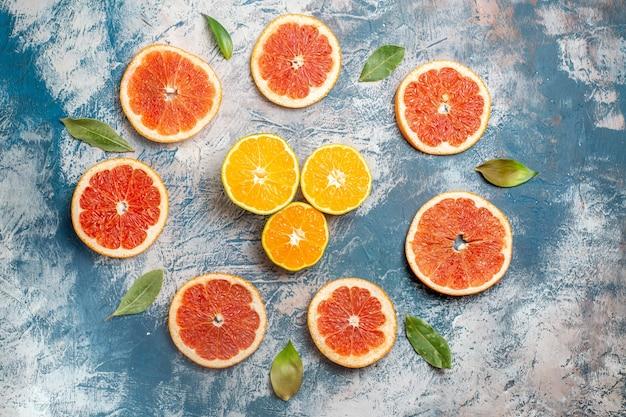 Vista dall'alto cerchio riga tagliata pompelmi tagliata arance blu tavolo bianco Foto Gratuite