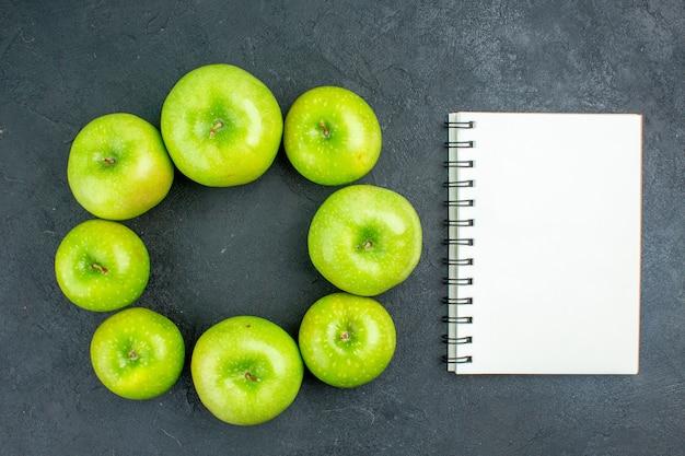 Вид сверху круглая строка зеленые яблоки ноутбук на темном столе Бесплатные Фотографии