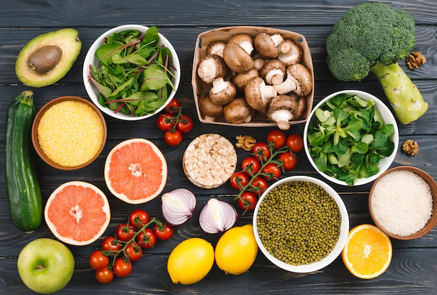 Top view of citrus fruits; vegetables and pulses on black table Free Photo