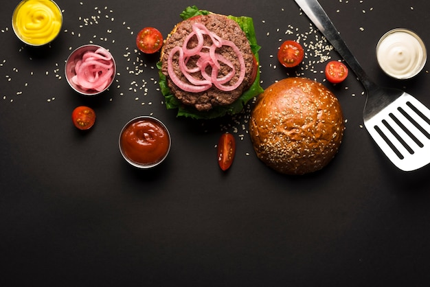 Top view classic burger surrounded by sauces Free Photo