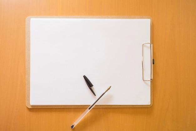 Top view of clipboard and pencil Free Photo