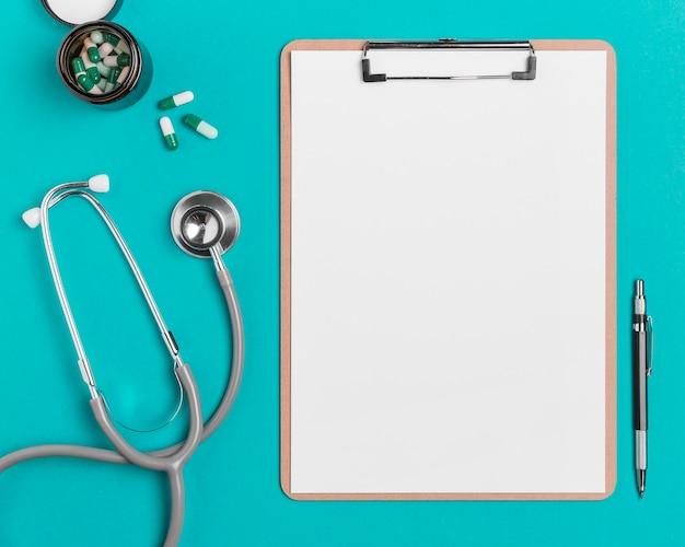 Appunti vista dall'alto con stetoscopio e pillole Foto Gratuite