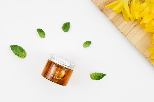 Top view close up shot jar of honey with flowers and leaves Free Photo