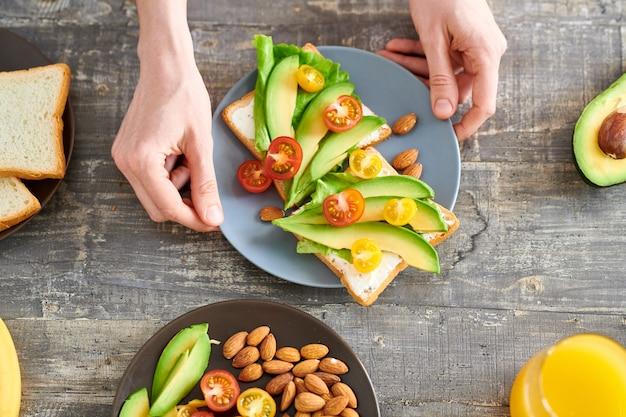 Крупным планом вид сверху неузнаваемой молодой женщины, делающей бутерброды с авокадо для здорового завтрака, копией пространства Premium Фотографии