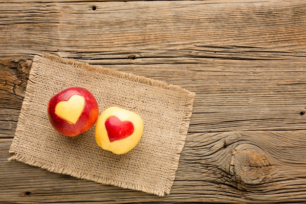 Top view of cloth and apple with fruit heart shapes and copy space Free Photo