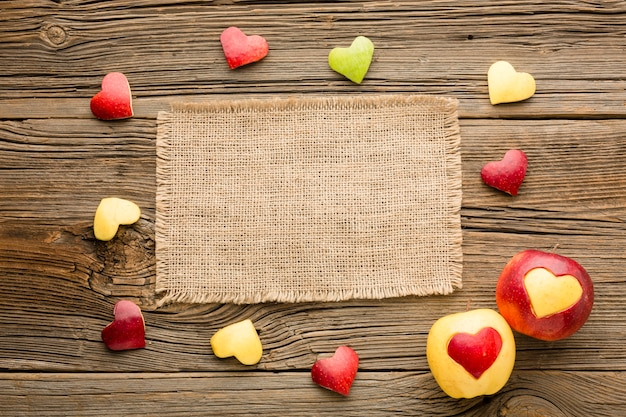Top view of cloth with fruit heart shapes Free Photo