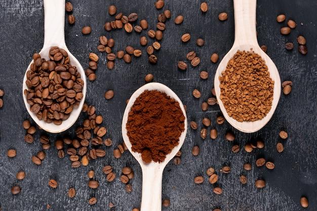 Кофе в зернах и растворимый кофе в деревянных ложках на темной поверхности Бесплатные Фотографии