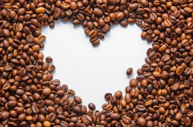 흰색 바탕에 빈 심장 모양으로 상위 뷰 커피 콩. 수평 무료 사진