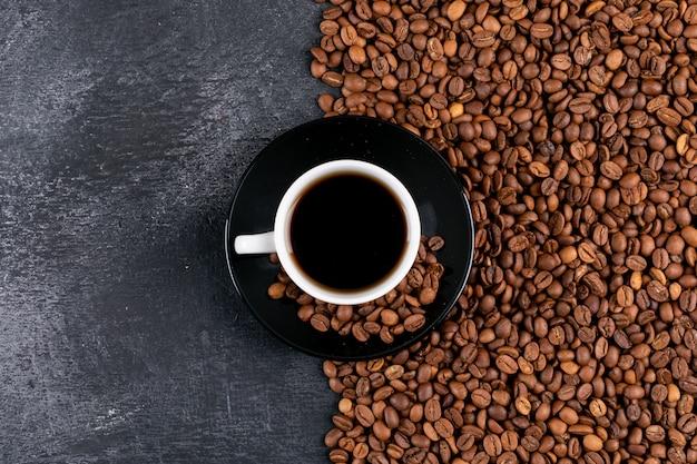 Tazza di caffè e chicchi di caffè di vista superiore sulla tavola scura Foto Gratuite