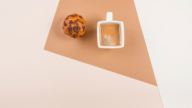 Top view of coffee cup and muffins on colored background Free Photo