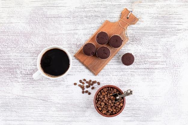白いテーブルの上のコーヒー豆とチョコレートのマフィンのトップビューコーヒーカップ 無料写真