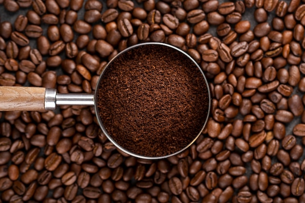 Top view coffee powder in strainer on coffee beans Premium Photo