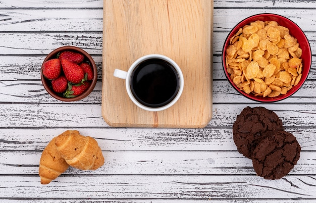 Top view of coffee with cookies and croissants, cornflakes with strawberry on white wooden surface horizontal Free Photo