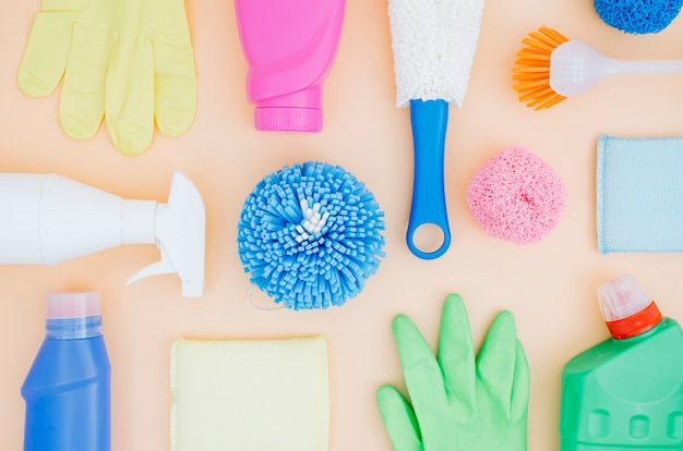 Top view collection of colorful cleaning supplies on peach background Free Photo
