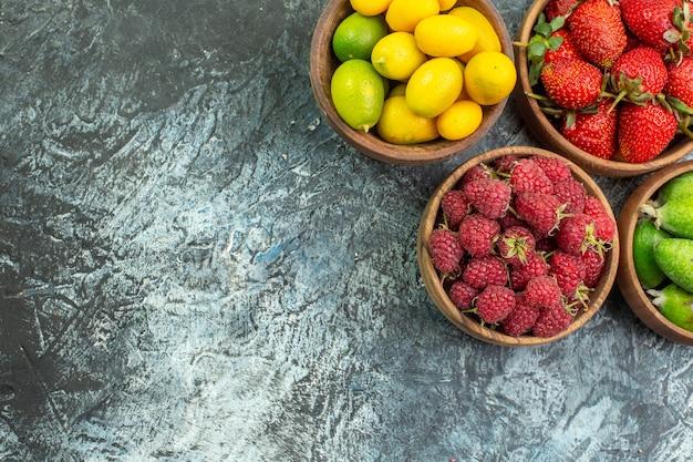 Vista dall'alto della raccolta di frutta fresca in secchi sul lato sinistro su sfondo scuro Foto Gratuite