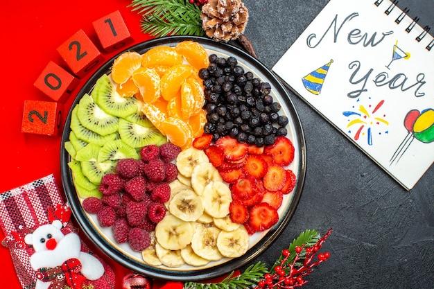 Vista dall'alto della raccolta di frutta fresca sugli accessori della decorazione del piatto della cena rami di abete e numeri calza di natale su un tovagliolo rosso prossimo taccuino con disegni di capodanno su sfondo nero Foto Gratuite
