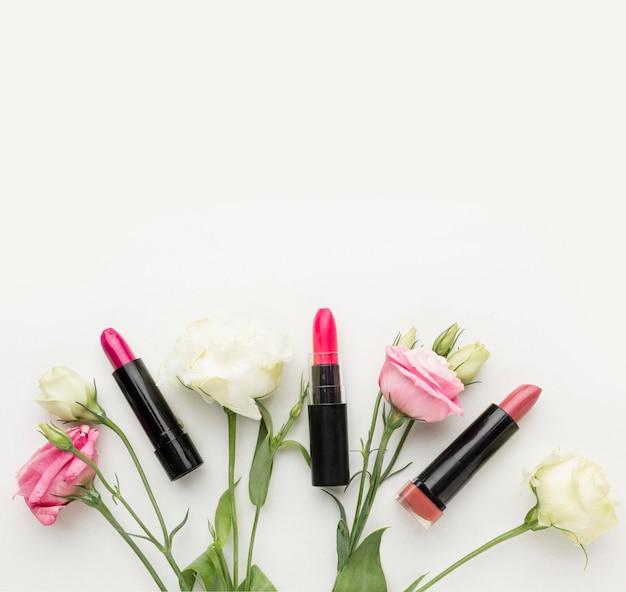 Collezione vista dall'alto di rossetto e fiori con spazio di copia Foto Gratuite
