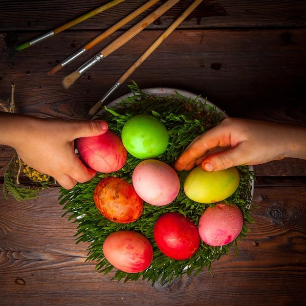 トップビュー白い板で精液と人間の手で卵を着色 無料写真