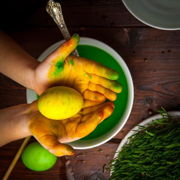 トップビュー着色された卵と精液と水と白いプレートに人間の手 無料写真